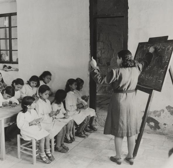 'Arab woman teaches children to read and write, Jerusalem'       A photograph of an Arab woman teaching children in Jerusalem, taken in 1945 by Jack Esten for the Daily Herald