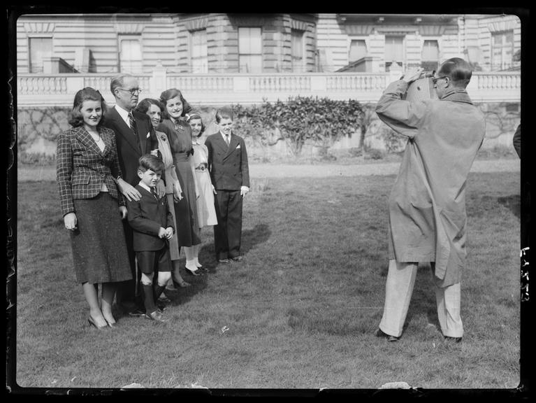 Joe and Rose Kennedy and Family pose for a news camera, London       A photograph of Joseph and Rose Kennedy and family posing for a news camera in London