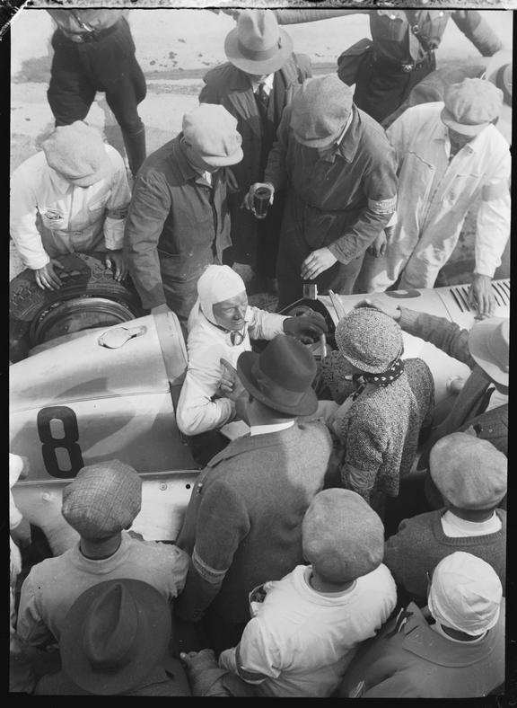 Hanns Geier surrounded by people in his Mercedes-Benz racer, Nurburgring