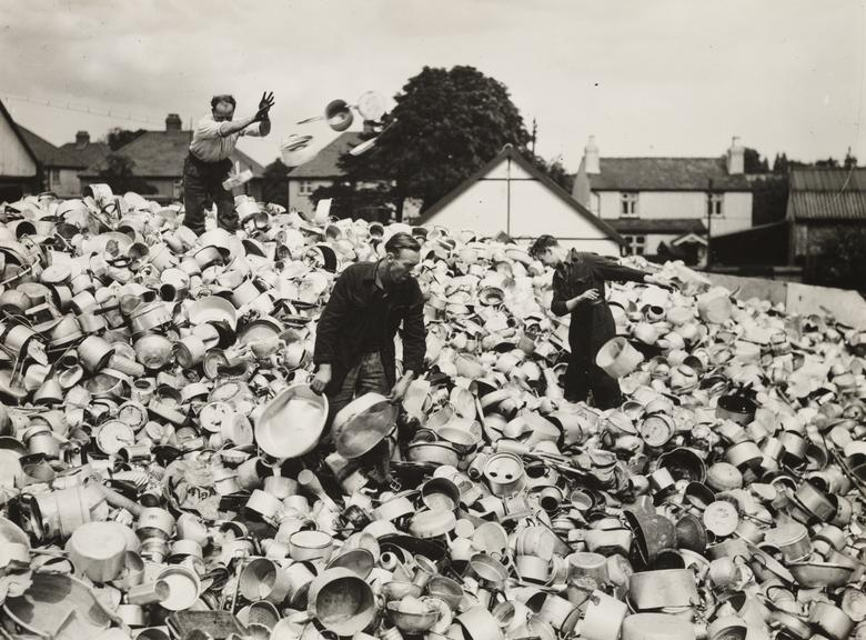 Collecting aluminium pots and pans to make aeroplanes       A photograph of men working on a huge mound of aluminium pots, pans and other domestic items