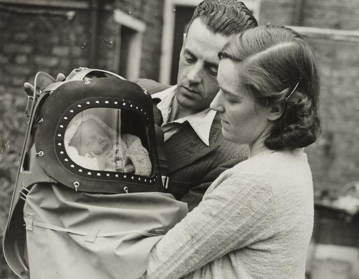 'First War Baby Gets His Gas Mask'       A photograph of Neville, the first baby born in London after the declaration of war