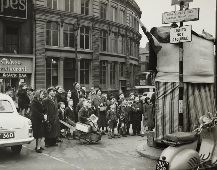 Punch and Judy theatre, Liverpool       A photograph of a crowd of people watching a Punch and Judy show in Liverpool