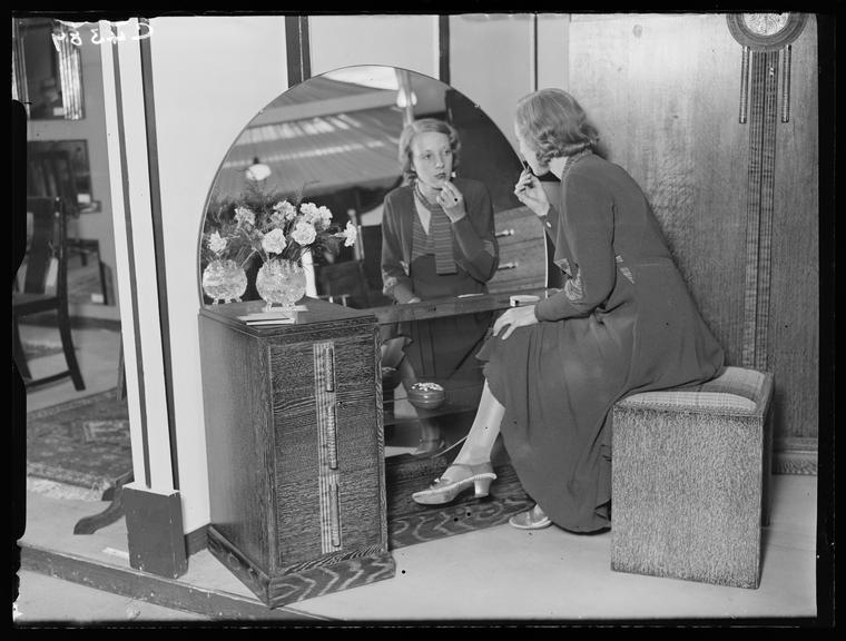 Furniture Exhibition at Dorland Hall, Regent Street       A photograph of a woman sitting at a dressing table at an exhibition (probably the 'Exhibition of British Industrial