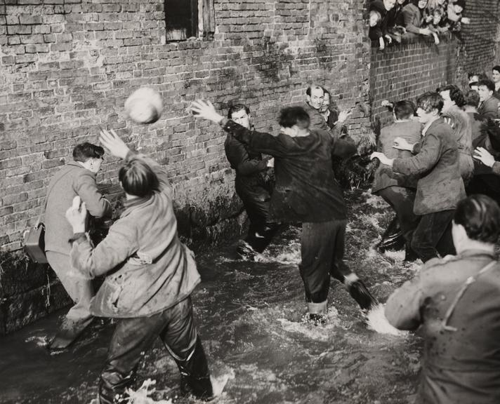 'Shrovetide Football at Ashbourne'       A photograph players fighting for possession of the ball in Henmore Brook during Shrovetide football in the village of