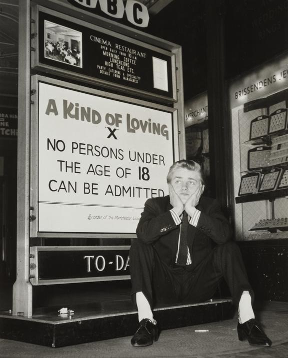 Malcolm Patton sits outside a cinema showing 'A Kind of Loving'       A photograph showing Malcolm Patton sitting outside a cinema showing 'A Kind of Loving'