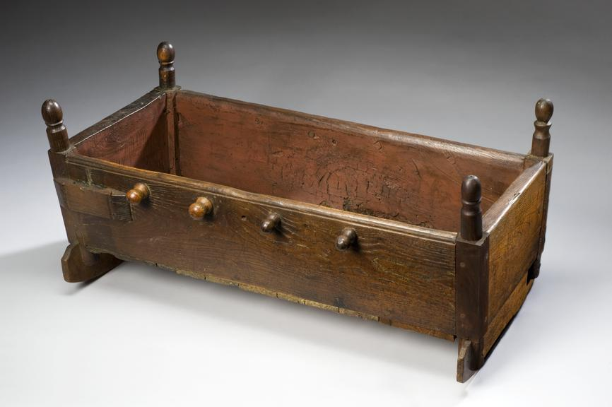 Rocking cradle, oak and pine, Europe, 1750-1850.       Full 3/4 view, graduated grey background.
