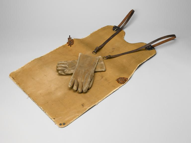 (A606875) Lead apron, for use as protection for X-ray technician, 1920 to 1958, and (A606876) Pair of lead gloves, for