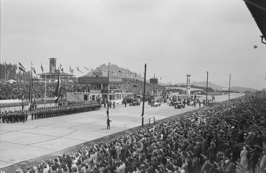 The crowd gives Hitler salute as soldiers parade at Nurburgring race track