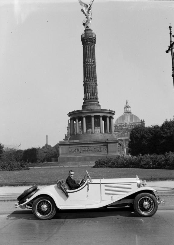 Man in white car in front of Victory Monument, Berlin