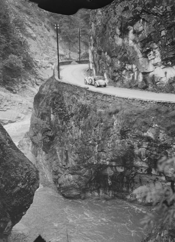 Car driving on a road cut into a mountain and above a river