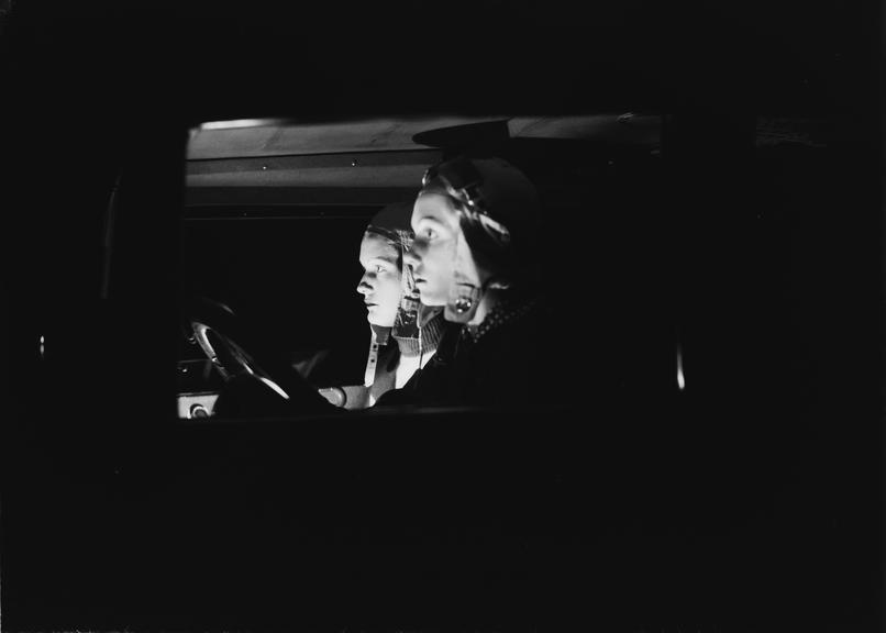 Side view of two women in a car at night