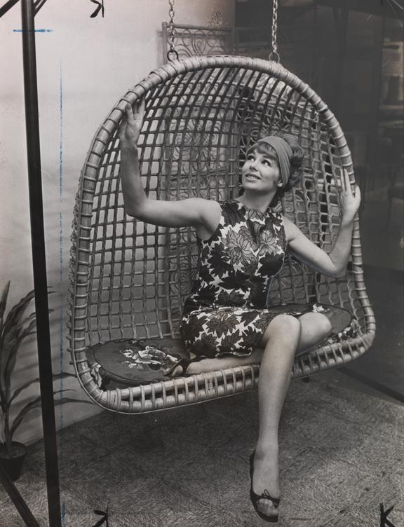 Woman posing on a Qualicane swinging seat       A photograph showing a woman posing on a Qualicane swinging seat