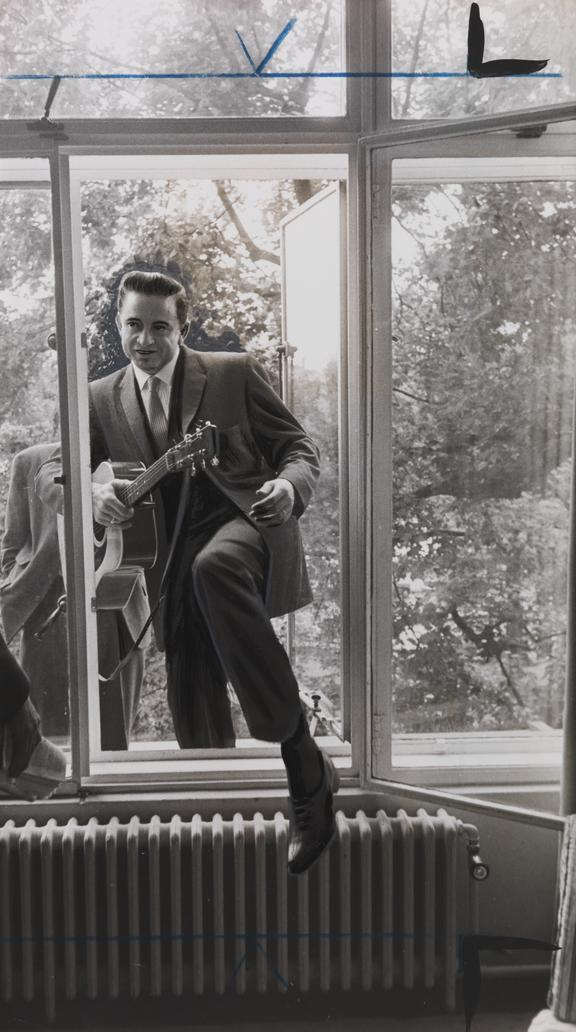 Johnny Cash with Guitar       A photograph of Johnny Cash (1932-2003) climbing through a window, guitar in hand