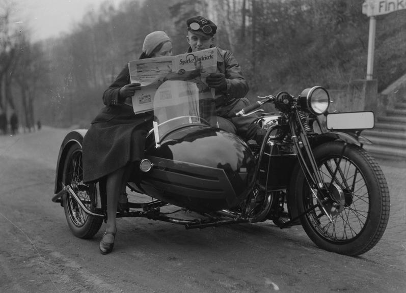 A man and woman read a copy of 'Sport Illustrierte' sitting on a motorcycle