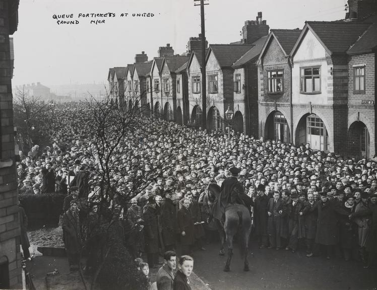 'Scene after stampede for tickets to see football club Manchester United'       A photograph showing the scene after a stampede for tickets to watch Manchester United