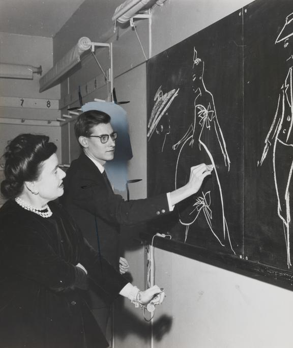 Yves Saint Laurent draws fashion designs on blackboard       A photograph showing Yves Saint Laurent (1936-2008) drawing fashion designs on a blackboard