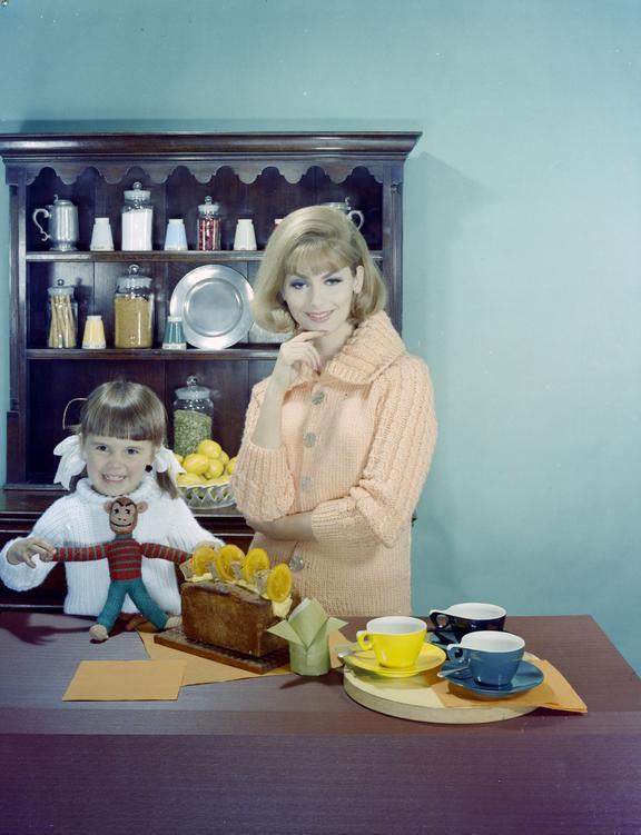 Woman & child wearing knitwear pose beside tea things