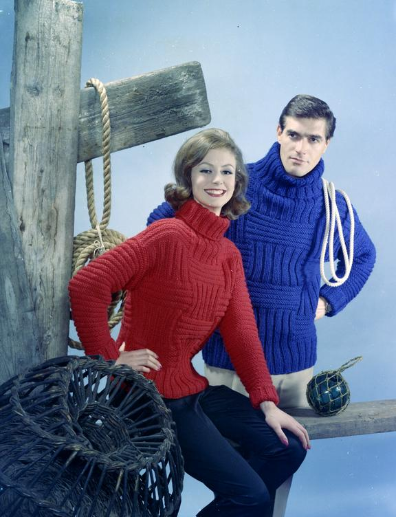 Couple in knitted jumpers pose next to fishing props