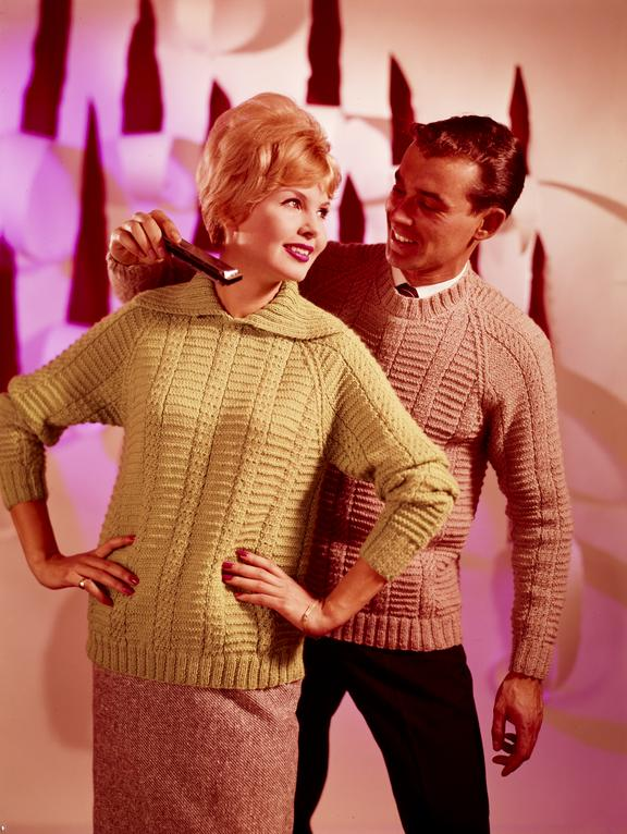 Man wearing knitted jumper holds harmonica up to similarly attired woman