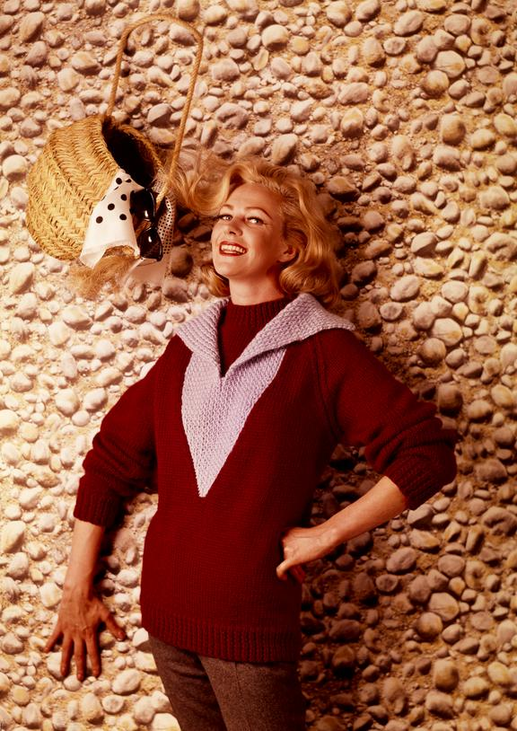 """Woman wearing knitted jumper poses against cobbled """"wall"""" with woven bag"""