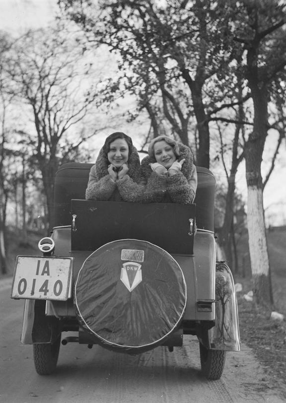 Two women posing in the boot of a DKW car