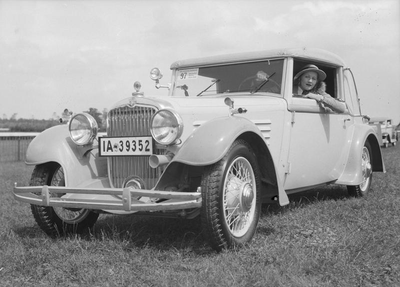 Woman in a Steyr car - entry no. 97 - at an automobile show