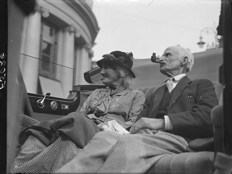 'Elderly country couple sit in car during London trip'       A photograph entitled 'Elderly country couple sit in car during London trip'