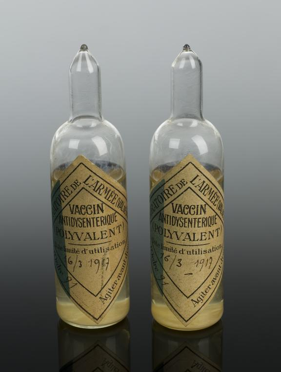 Ampoules, 2, of dysentery vaccine, by Laboratoire de l'Armee, French, c. 1916. Graduated black perspex background.