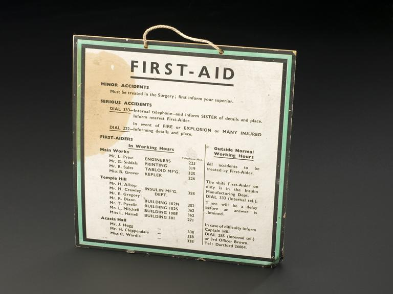 First aid notice, cardboard, English, 1901-1950.  Front 3/4 view of whole object on graduated grey background