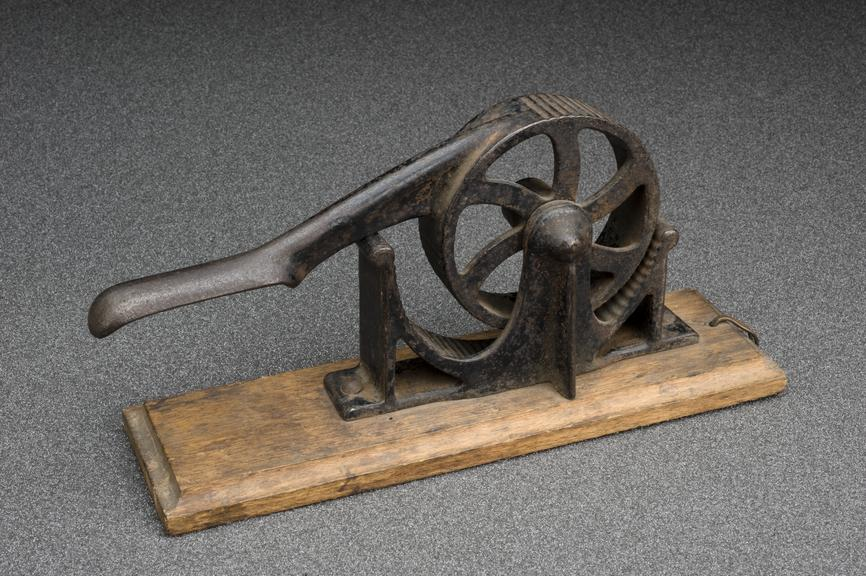 Rotary cork presser, probably late 19th century. Graduated textured grey background.
