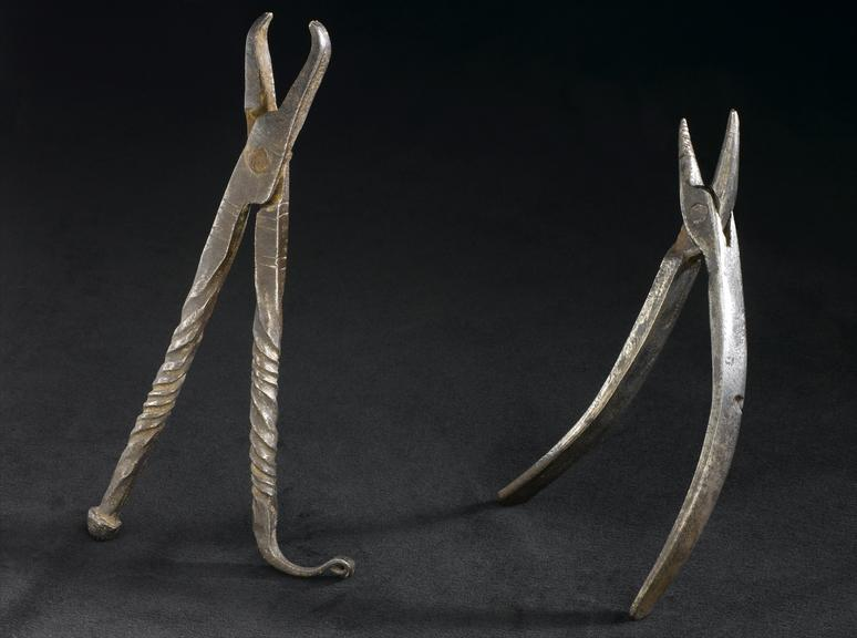 Group shot on dark backgrund showing from left to right A621720 Dental forceps, very crude construction, iron, probably