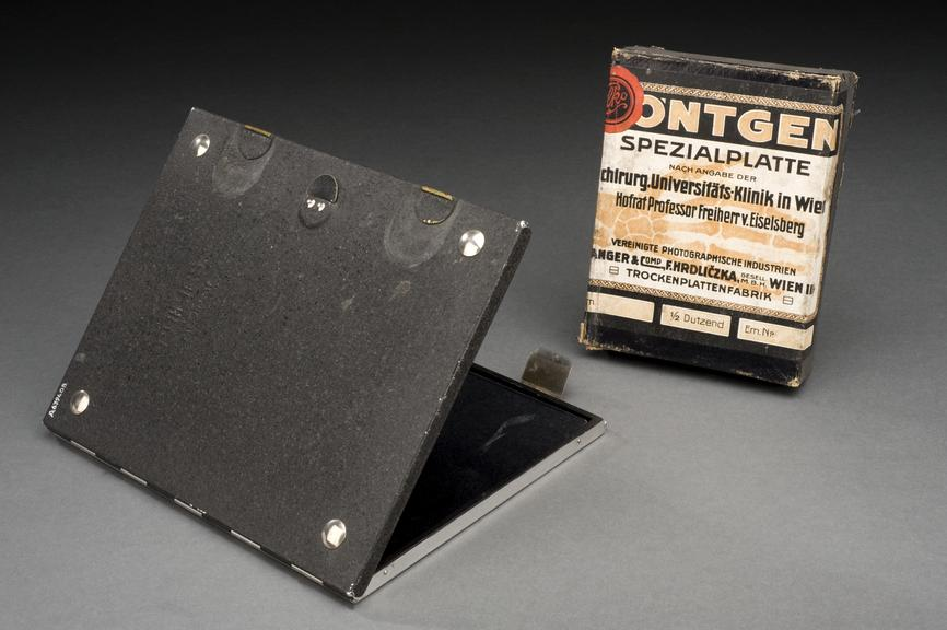Left hand side: A639408 Pt10, Film holder. Right hand side: A655772 Pt6, Box of X-ray plates. Graduated grey background.
