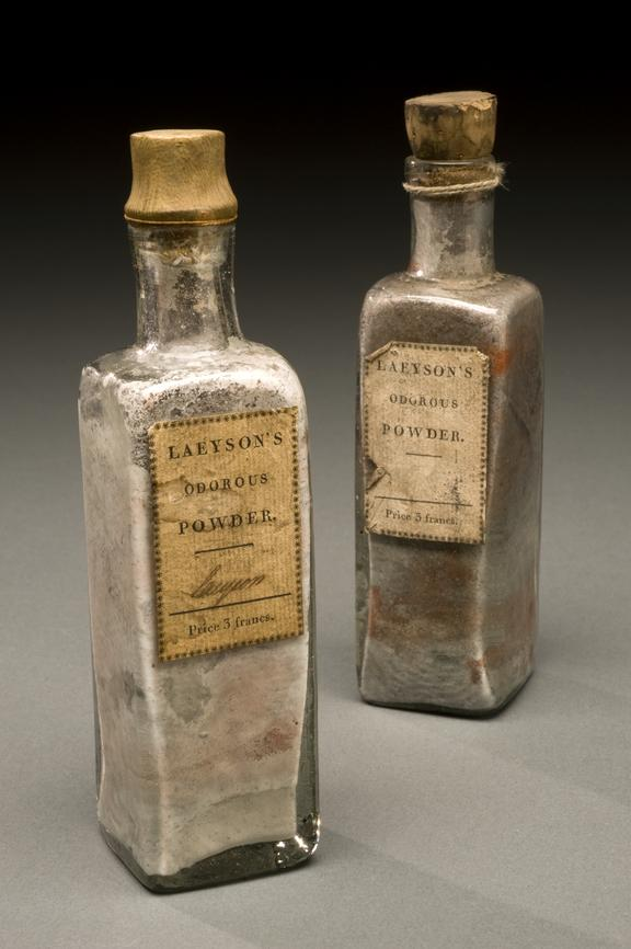 """Two bottles of """"Lacyson's Odorous Powder"""" Graduated grey background."""