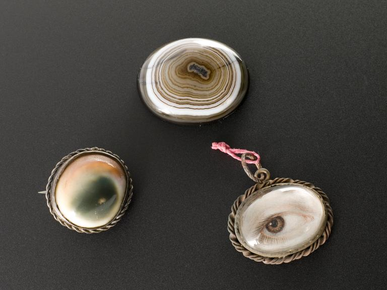 Group shot of from left to right A665895 - Amuletic pendant, eye painted on shell in oval metal mount, glazed, with