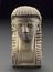 """1 Plaster cast of Egyptian head 3 1/4"""" xx 1 5/8.  Front view of whole object against graduated grey background."""