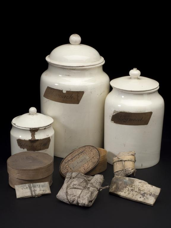 "Group of objects from Watt Workshop.  Jar of  ""Shumach""  (1924-792/1481), rear centre; Cream ceramic jar labelled"