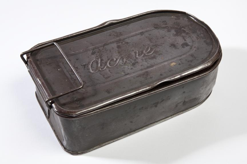 Miner's snap tin, metal, 'Acme' brand. Bought frin Uppermill Fair, November 1981.Photographed 3/4 view on a white