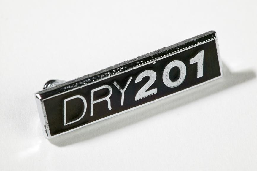 Dry 201 lapel badge, produced in about 1989.Photographed on a white background.