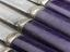 Six butter knives with purple Parkesine handles; steel blades, Made by Alexander Parkes; c.1862. Detail view. Grey