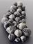 28 Oak galls, burnt black. Portrait format close up view. Graduated grey background