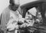 Stirling Moss signs an autograph for Christopher Carson at Goodwood, 1960.       This is a fully retouched and clean,