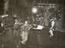 A young boy stands on the hotel reception desk of the Ritz Royal surrounded by guests and co-workers in a film scene,