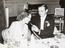 Marlene Dietrich and unknown gentleman smoking at dinner, not dated