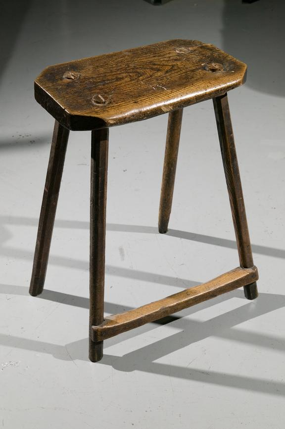 Wooden stool, c.1835. Four legged stool, with octagonal seat. Each leg is wedged into the hole in the seat. There is