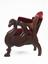 This early adjustable dental chair has plush upholstered seating with elaborate wooden carvings - the arms take the