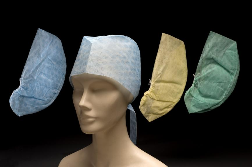Selection of 3 blue, 1 green and 1 yellow nurses disposable theatre caps. One placed on mannikin, others adjacent on