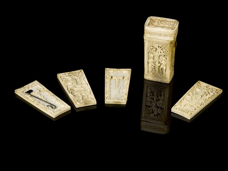 Bone fleam case, intricately carved with representation of the crucifixion and the Garden of Eden, containing four