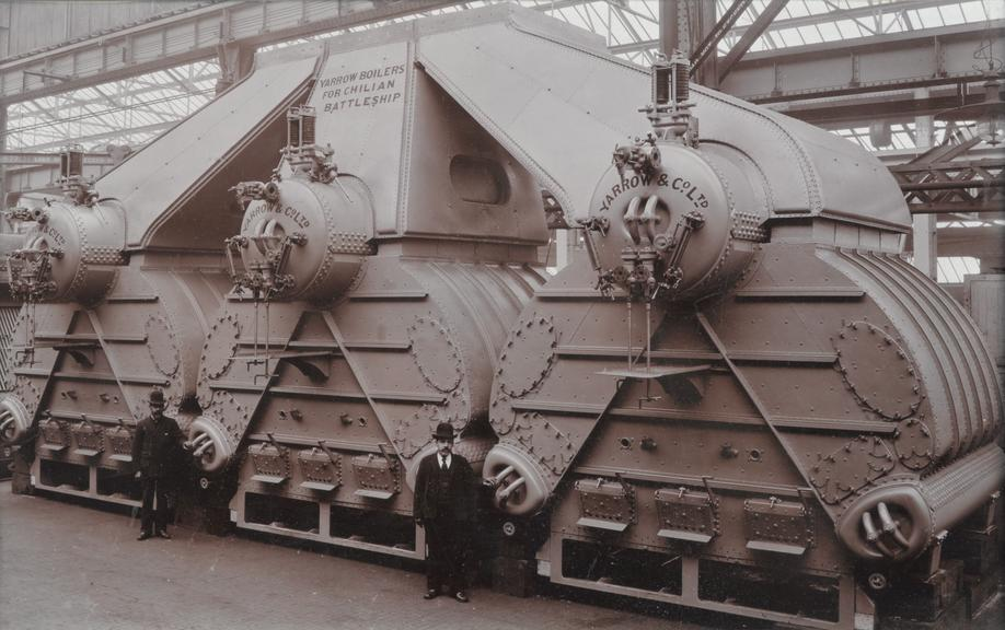 Monochrome photograph of a set of three full scale complete 'Yarrow' boilers, with two figures in business dress