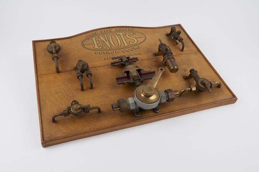Seven cork disc seated Enots' petrol cocks and two sectioned examples of same mounted on polished oak board, made by