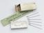 Packet of dried smallpox vaccine (1986-1658) with six bifurcated needles for smallpox vaccination (1979-61). Top three